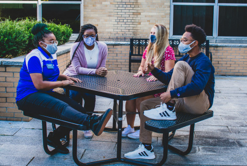 Students in masks sitting at a table outside of the RIC