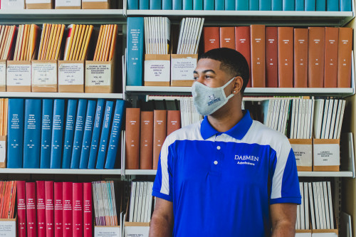 Male Daemen student wearing a face mask standing in font of a row of books in the RIC