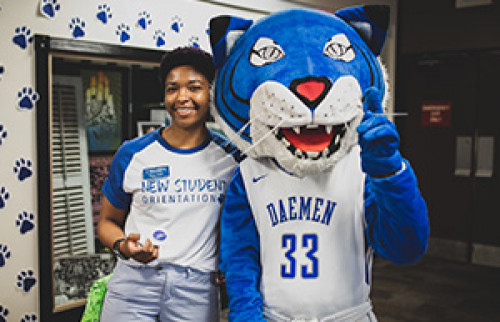 Willie the Wildcat and student in a New Student Orientation t-shirt