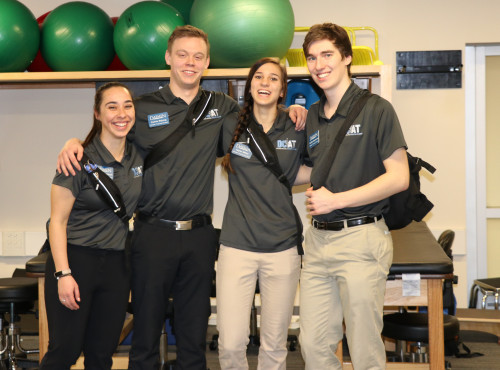 Athletic Training students arms around each others shoulders in the AT lab