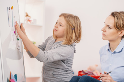 Therapist working with a child on a whiteboard