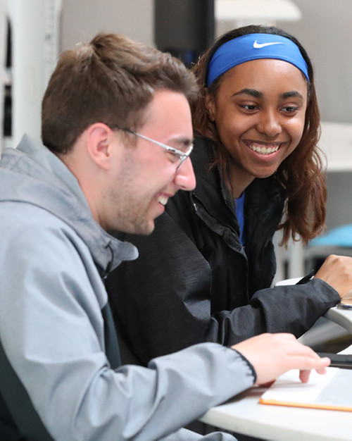 Two students working on their laptops, talking and smiling