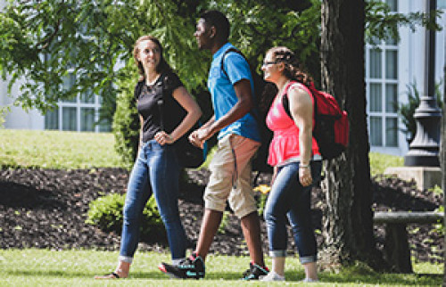 Three students walking on campus during the summer viewed from their left side