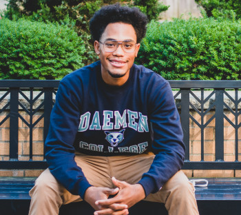 African American male student with glasses wearing a Daemen sweatshirt sitting on a bench