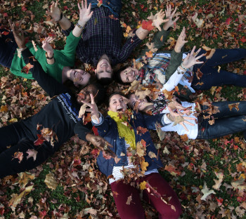 Circle of kids laying on grass throwing leaves in the air
