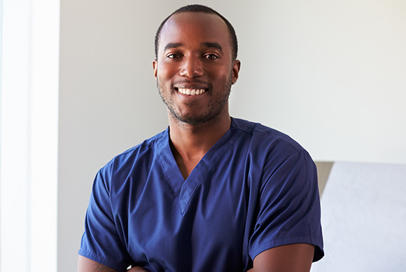 African American male in medical scrubs smiling with arms folded over chest